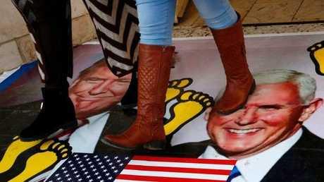 شابتان فلسطينيتان تدوسان على صورة ترامب وبينس