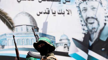 عنصران من حماس يقفان أمام صورة ضخمة للزعيم الفلسطيني الراحل ياسر عرفات في غزة