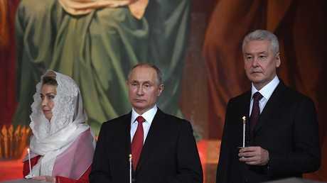 الرئيس الروسي فلاديمير بوتين وعمدة موسكو سيرغي سوبيانين أثناء صلاة عيد الفصح في كاتدرائية المسيح المخلص في موسكو