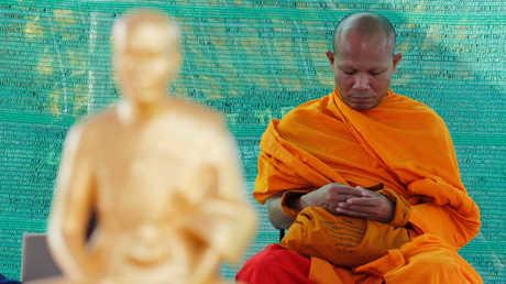 بوذي يؤدي طقوسا في أحد المعابد في تايلاند