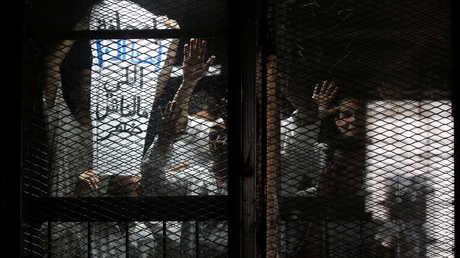 المصور الصحفي المصري محمود أبو زيد (يمين) خلف القضبان أثناء مثوله أمام القضاء في محكمة بضواحي القاهرة