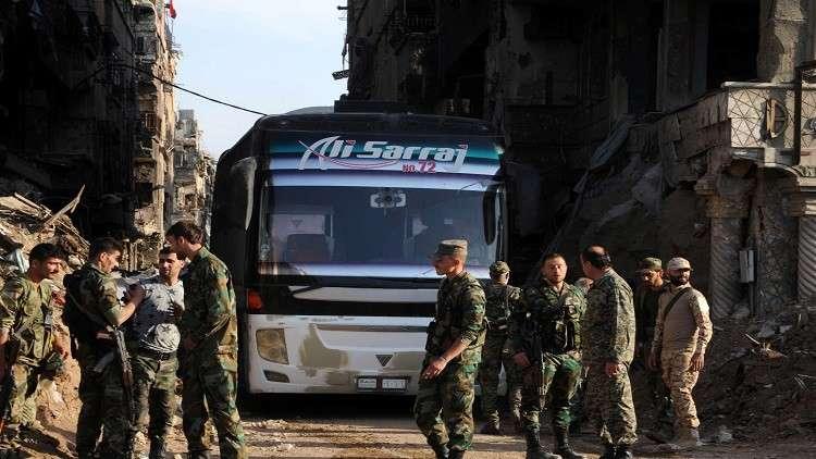 2556 مسلحا مع ذويهم يغادرون مخيم اليرموك بدمشق