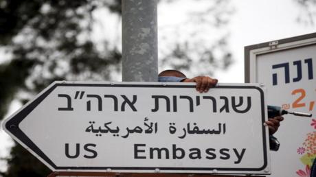 عامل يثبت لافتة تشير إلى اتجاه مبنى القنصلية الأمريكية في جنوب القدس