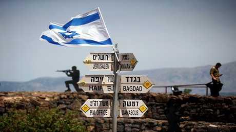 جندي إسرائيلي يقف في نقطة مراقبة بالجولان بجانب لافتات تشير إلى مسافات إلى مدن مختلفة