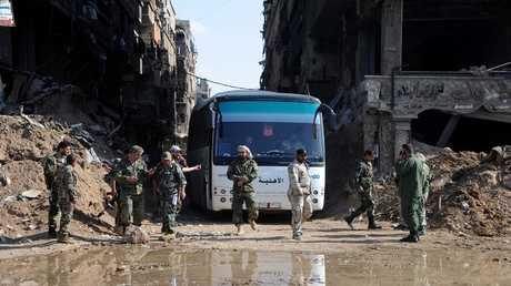 الجيش السوري يتابع إخراج المسلحين مع أفراد عائلاتهم من مخيم اليرموك على متن حافلات