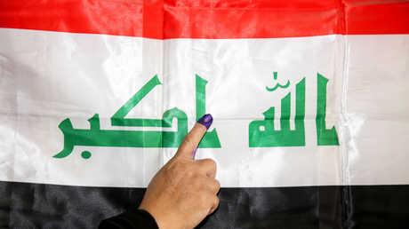 مشاركة في الانتخابات البرلمانية العراقية تشير بإصبعها إلى علم العراق