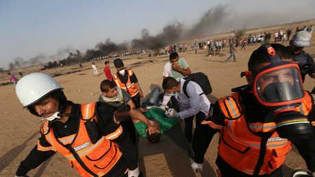 مسعفون يقومون بإجلاء احد جرحى الاعتداءات الإسرائيلية على المتظاهرين الفلسطينيين في غزة