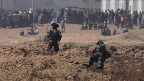 جنود إسرائيليون على يراقبون محتجين فلسطينيين على الحدود بين إسرائيل وقطاع غزة - أرشيف