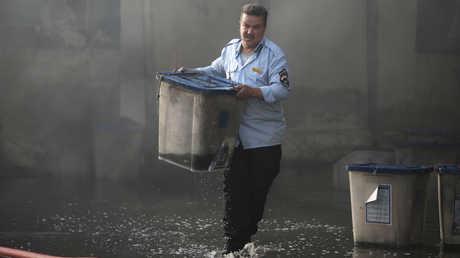 موظف يخرج صندوق اقتراع من مخازن المفوضية الانتخابية في بغداد