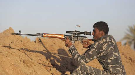 رجل يحمل سلاحا في العراق