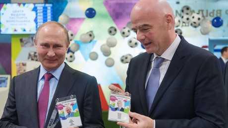 الرئيس الروسي، فلاديمير بوتين، ورئيس الاتحاد الدولي لكرة القدم، جياني إنفانتينو، يحملان طباقتيهما لهوية المشجع