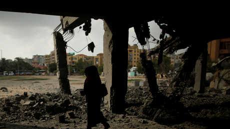امرأة فلسطينية أمام أنقاض مبان مدمرة جراء ضربة إسرائيلية على قطاع غزة