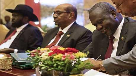 الرئيس السوداني عمر البشير (في الوسط) ورئيس جنوب السودان سلفا كير وزعيم المتمردين رياك مشار أثناء التوقيع على اتفاق وقف إطلاق النار، الخرطوم 27 يونيو 2018.