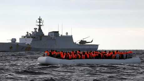 قارب لمهاجرين في البحر المتوسط قبالة سفينة البحرية الإيطالية