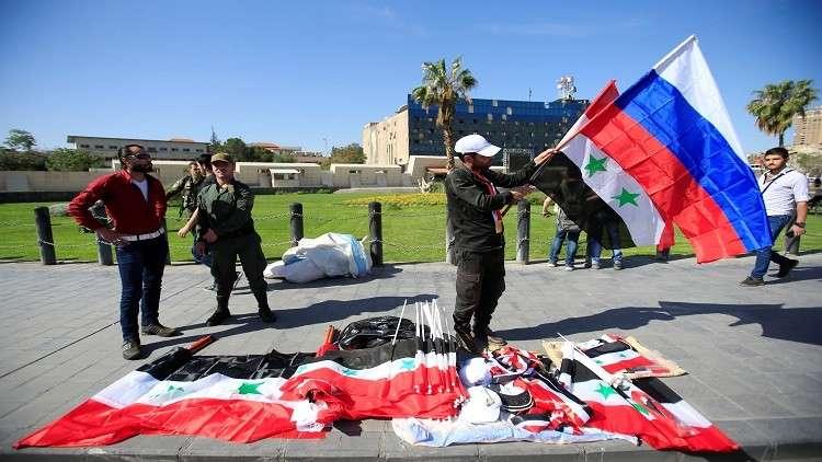 رجل يبيع الأعلام السورية والروسية على قارعة الشارع بدمشق، سوريا 16 أبريل، 2018