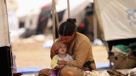 نازحة إيزيدية مع طفلتها