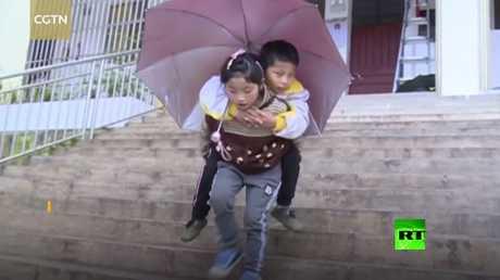 طفلة صينية تحمل شقيقها على ظهرها إلى مدرسة كل يوم