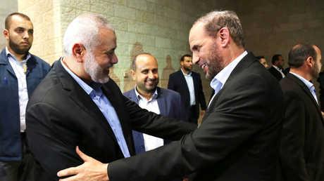 حسام بدران(يمين) يصافح رئيس المكتب السياسي لحركة حماس إسماعيل هنية
