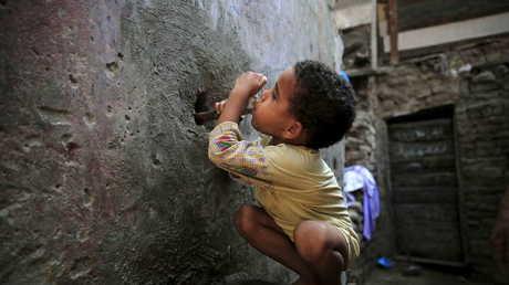 طفل يشرب الماء من صنبور بالشارع في حي بالقاهرة