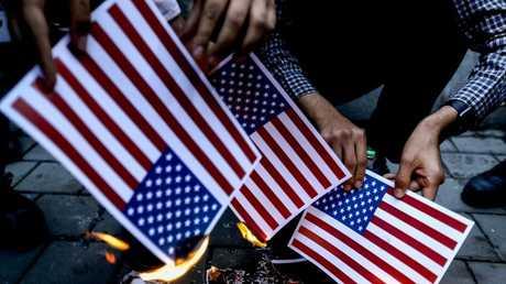 إيرانيون يحرقون أعلاما أمريكية احتجاجا على انسحاب واشنطن من الصفقة النووية