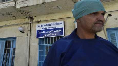 طبيب يقف خارج مستشفى في مدينة بوفاريك الجزائرية، 28 أغسطس 2018
