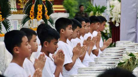12 تلميذا نجوا من كهف في تايلاند يزورون معبدا بوذيا