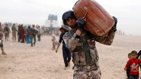 عسكري أردني يساعد لاجئين سوريين عالقين على الحدود بين البلدين (أرشيف)