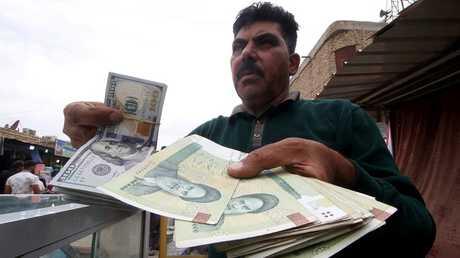 رجل عراقي يحمل أوراقا نقدية إيرانية في البصرة، 3 نوفمبر 2018