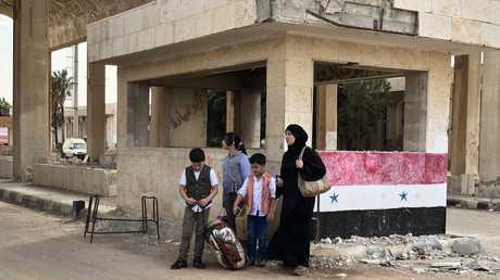 امرأة وأطفالها قرب معبر نصيب على الحدود مع الأردن