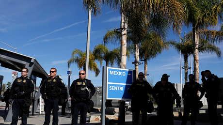 أفراد من القوات التابعة لوزارة الأمن الداخلي الأمريكية يراقبون المهاجرين من أمريكا الوسطى عند معبر سان إيسيدرو الحدودي مع المكسيك