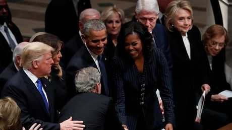 جورش بوش الابن أثناء مصافحة قرينة باراك أوباما