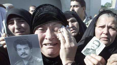 أرشيف - نساء عراقيات يحملن صوراً لأبنائهن الذين قيل إنهم فقدوا في الكويت خلال حرب الخليج عام 1991 - بغداد، 31 أكتوبر 2001