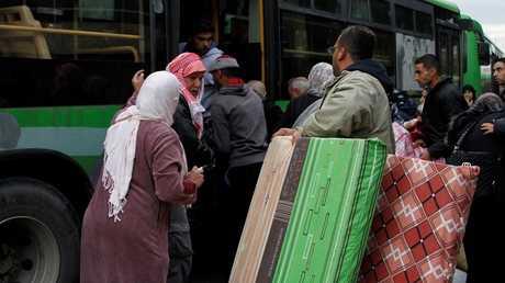 لاجئون سوريون يركبون حافلة عائدين إلى سوريا من مدينة طرابلس اللبنانية