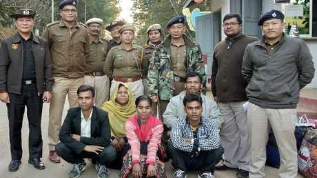 عائلة من الروهينغا تجلس أمام مسؤولين أمنيين من الهند وميانمار