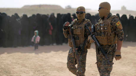 عناصر من قوات سوريا الديمقراطية أثناء خروج مدنيين من الباغوز