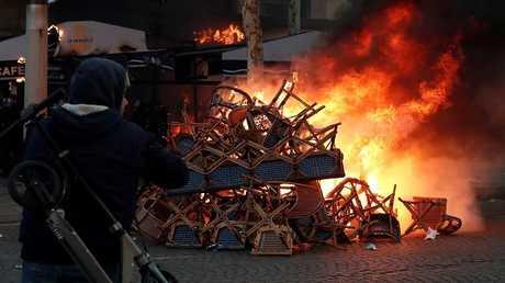 مواطن فرنسي يقف امام واجهة محل تحترق في الشانزيليزيه بباريس