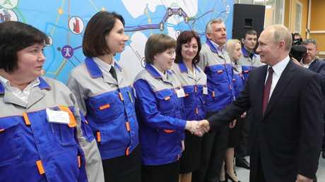 الرئيس الروسي فلاديمير بوتين خلال مصافحته العاملات في المحطة الحراراية