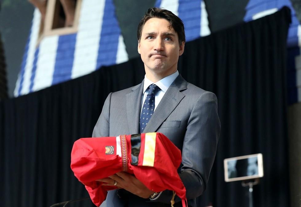 رئيس الوزراء الكندي جاستن ترودو حاملا تقرير الإبادة الجماعية