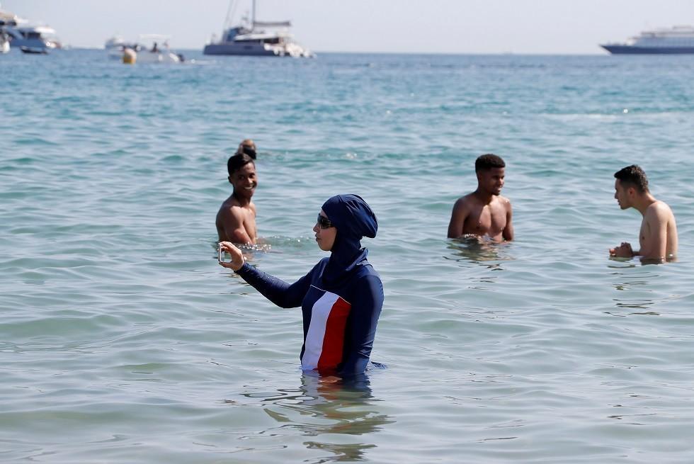 فتاة ترتدي البوركيني في البحر - ارشيف