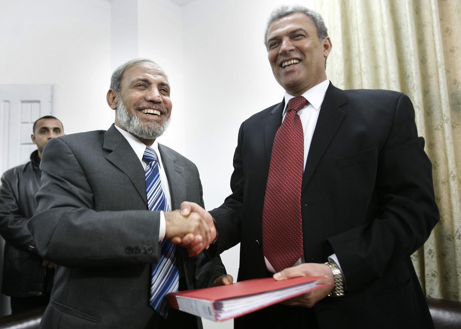 زياد أبو عمرو يصافح القيادي في حماس محمود الزهار في لقاء سابق