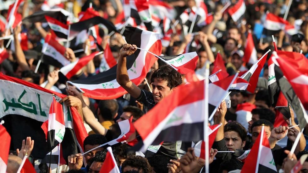 عراقيون يحملون العلم في إحدى المظاهرات وسط بغداد - أرشيف
