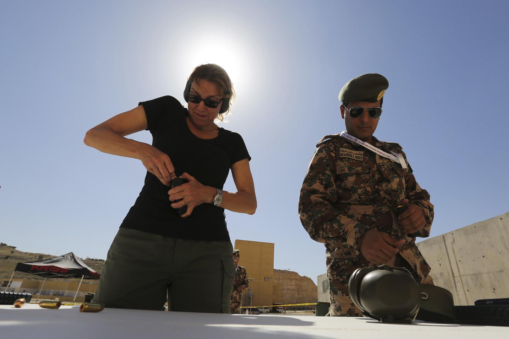 جندي  أردني إلى جانب عضوة من وفد أمريكي تستعد لإطلاق النار من سلاح أوتوماتيكي جديد في مسابقة المحارب السنوية السادسة في مركز الملك عبدالله للتدريب على العمليات الخاصة في عمان