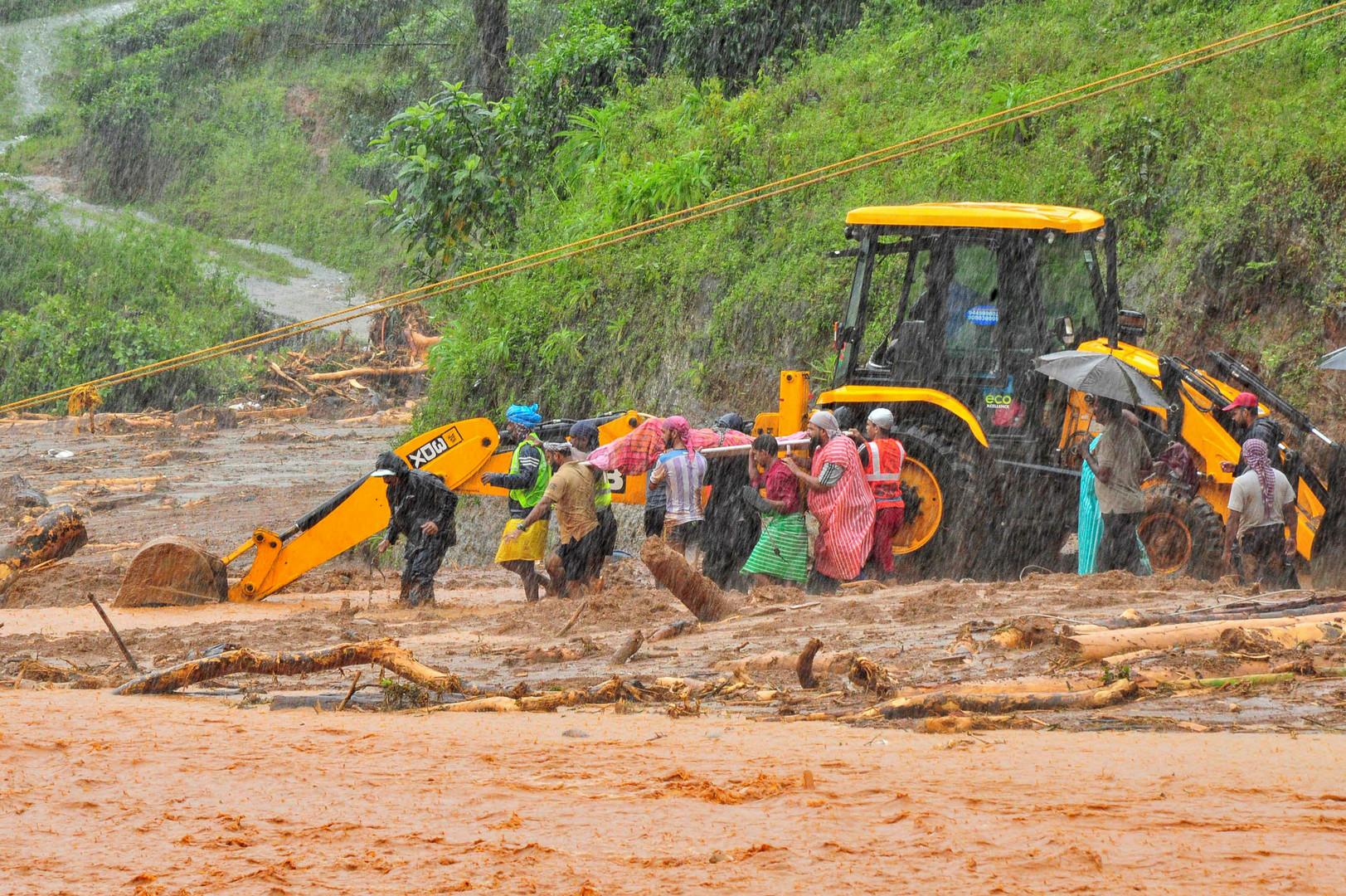 منقذون يحملون جثة أحد ضحايا انزلاق طيني في ولاية كيرلا الهندية