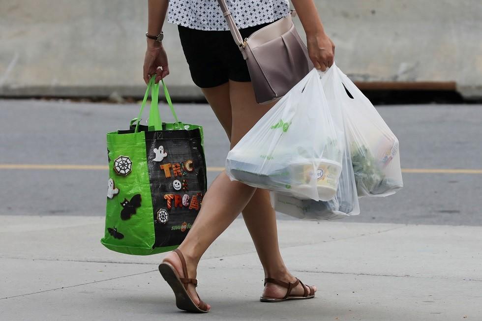 زبون يحمل أكياسا بلاستيكية بعد التسوق