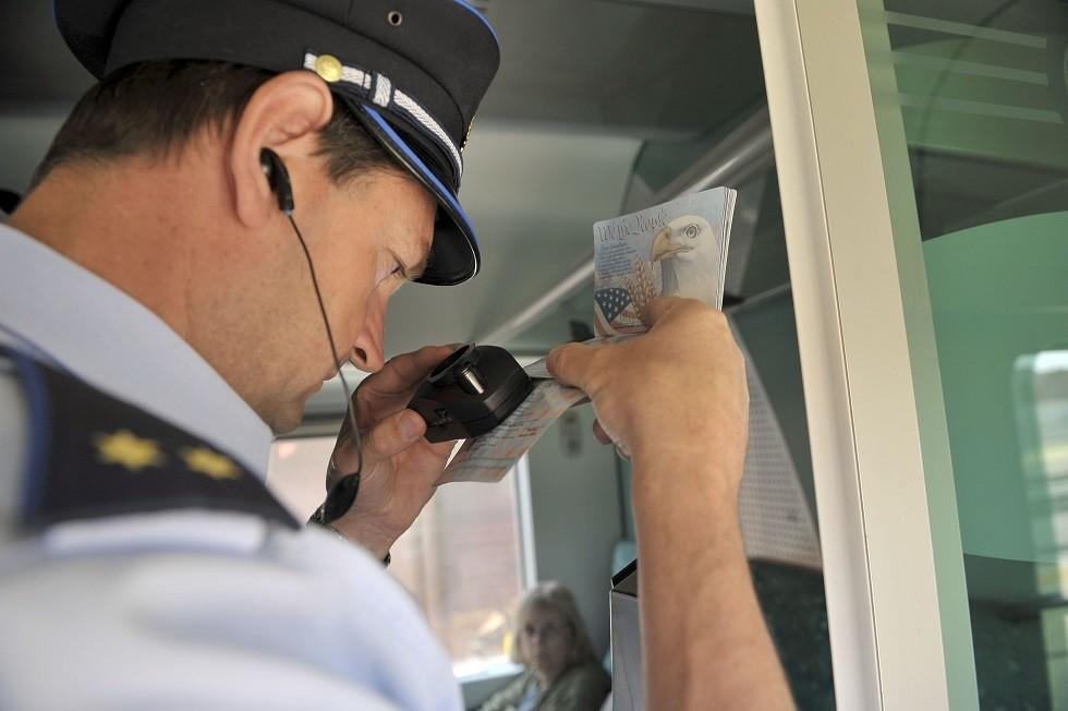 أرشيف - شرطي يتفحص جواز سفر على الحدود بين سلوفينيا وكرواتيا