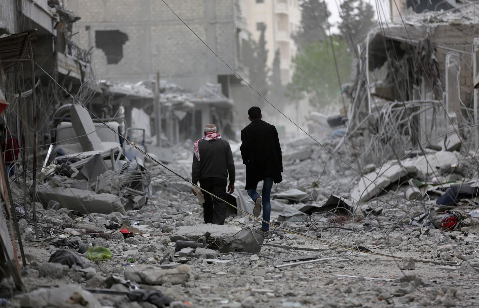 شخصان يمشان وسط أنقاض مبان مدمرة وسط مدينة عفرين شمال سوريا