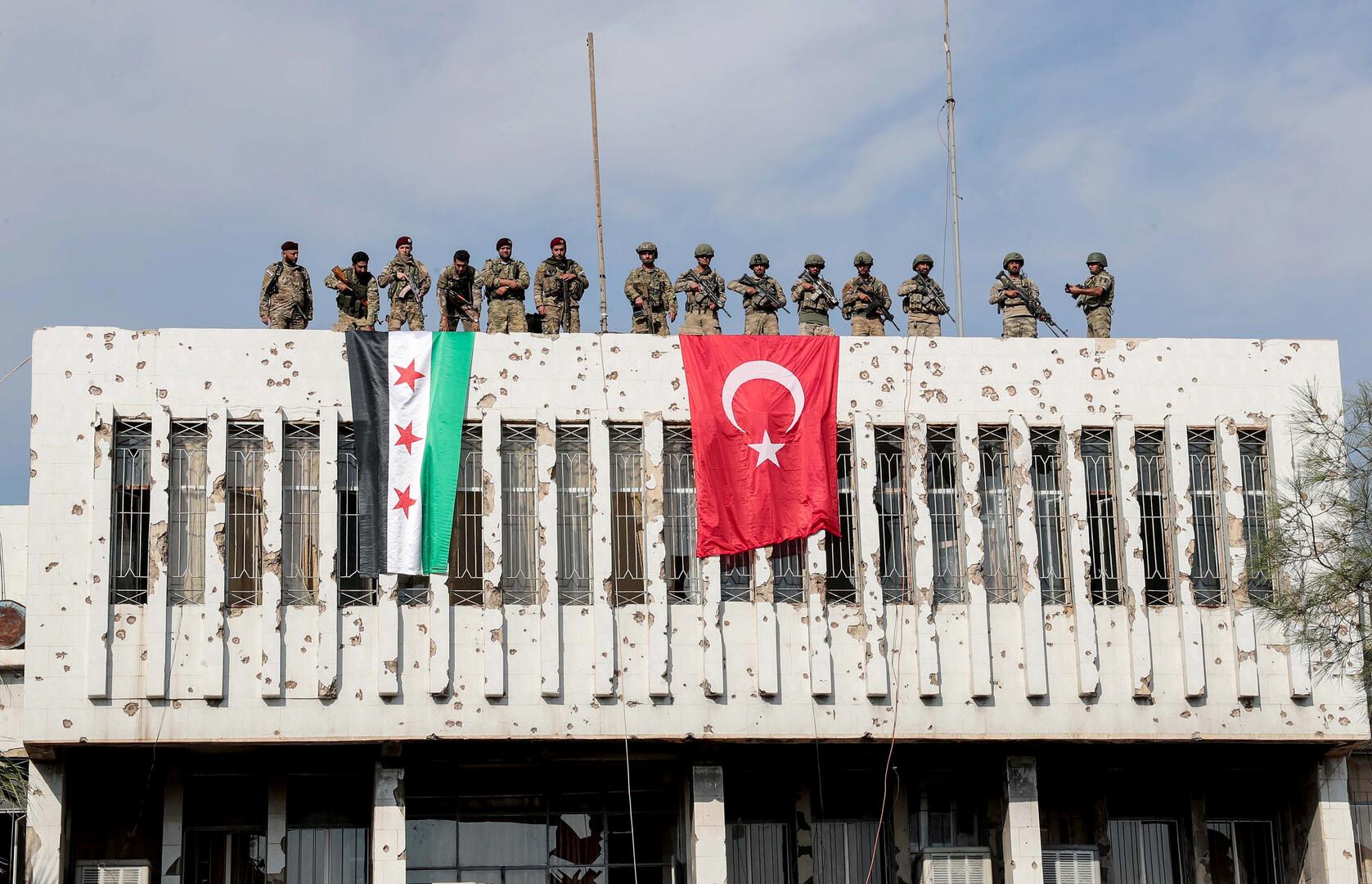 عناصر من الجيش التركي والمعارضة السورية المسلحة على سقف مبنى في مدينة رأس العين شمال شرق سوريا