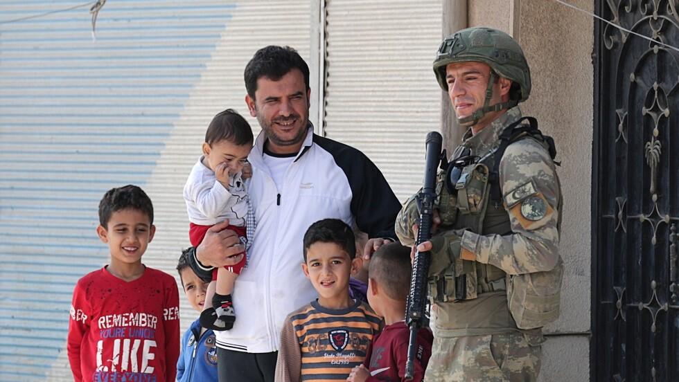 جندي تركي مع سكان في تل أبيض