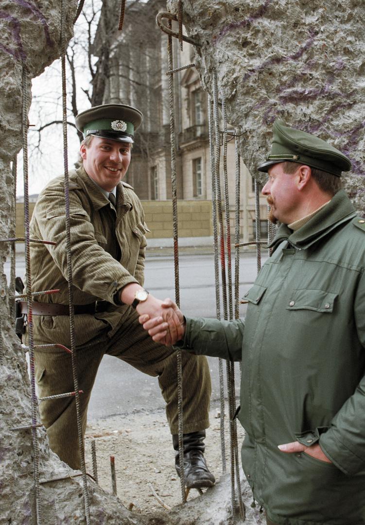 عسكري من ألمانيا الشرقية وآخر من الغربية يتصافحان عبر ثغرة في حائط برلين