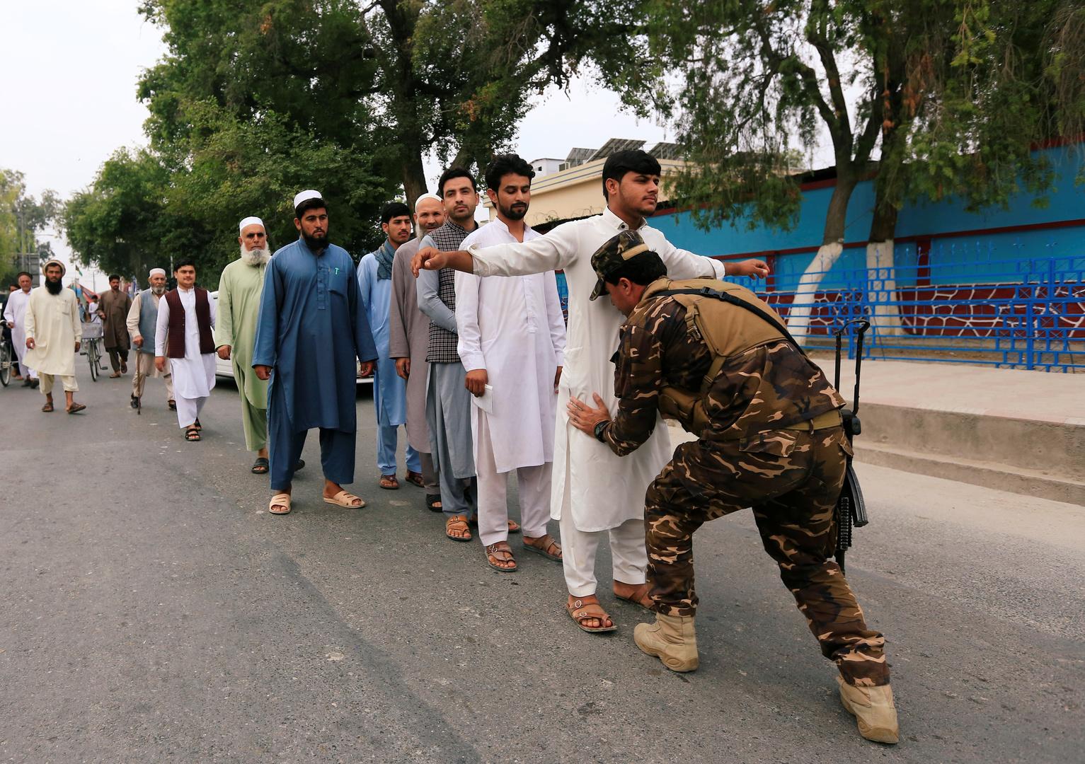 عنصر من الأمن الأفغاني يفتش الناخبين الراغبين في الإدلاء بأصواتهم في انتخابات الرئاسة 2019 في مدينة جلال آباد